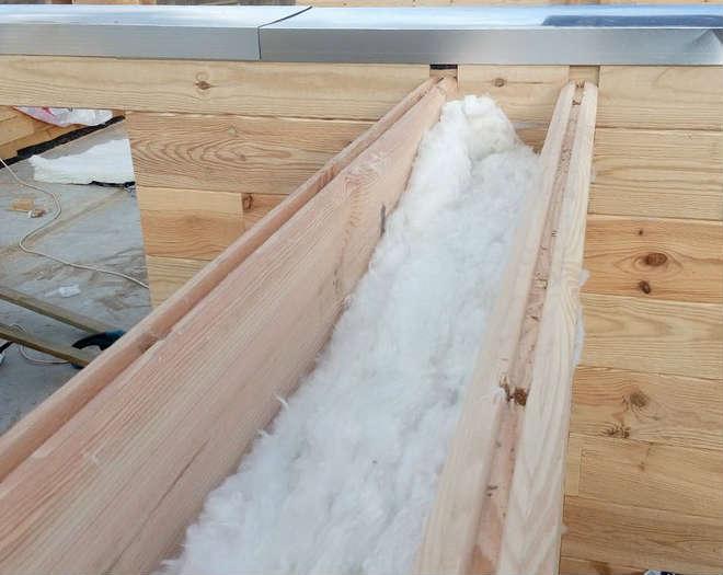 Укладка утеплителя в пространство стены из двойного бруса